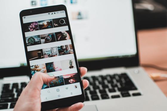 Телефон с открытой социальной сетью в руке