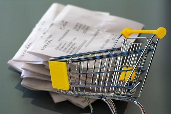 Крзина для покупок стоит на фоне стопки чеков