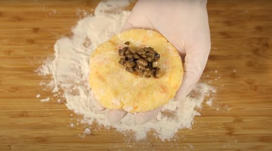 Лепешка из картофеля с грибной начинкой в руке