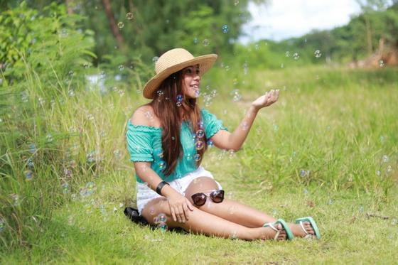 Девушка сидит на лужайке, окруженная мыльными пузырями
