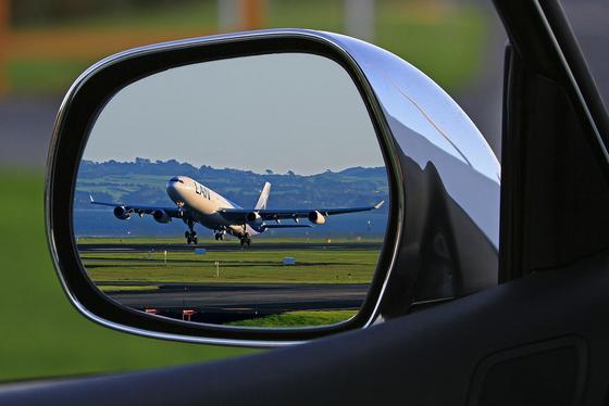 Самолет отражается в зеркале автомобиля