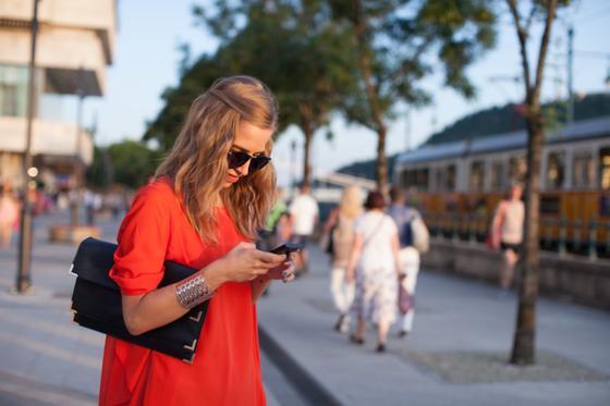 Девушка в красном платье смотрит в телефон