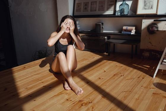 Девушка в комнате закрывает глаза от солнца, сидя на полу