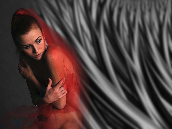 Девушка обнимает себя руками под красной шалью