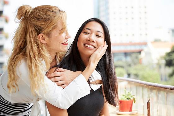 Две девушки обнимают друг друга и улыбаются