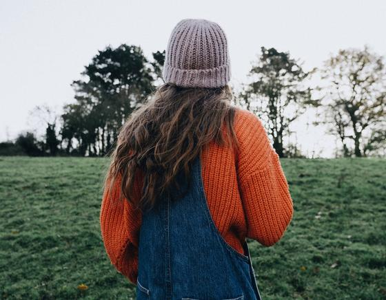девушка в свитере и джинсовом комбинезоне