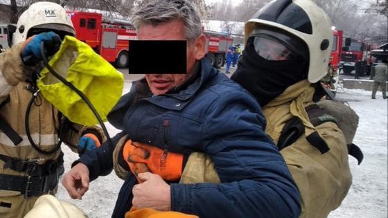 Пожарные выносят мужчину в синей куртке