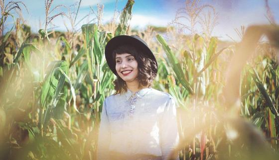 Девушка стоит на кукурузном поле