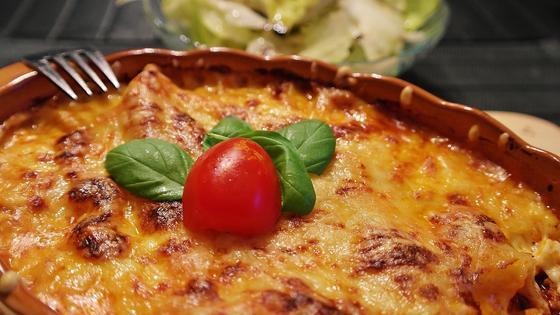 Лазанья, украшенная помидором черри и зеленью