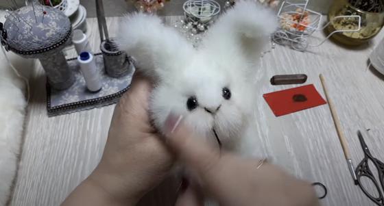 Женщина шьет из меха игрушку «Кролик»