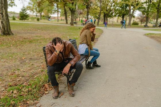 Мужчина и женщина сидят на лавочке в парке, отвернувшись друг от друга
