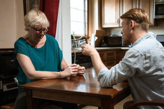 Мужчина сидит за столом напротив смущенной и обиженной женщины