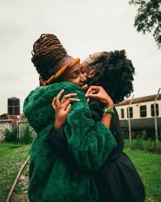 Девушки в зеленой одежде обнимаются