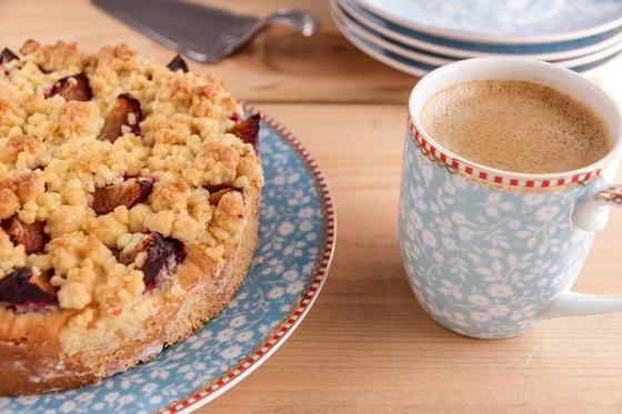 Песочный пирог на тарелке, рядом чашка с напитком