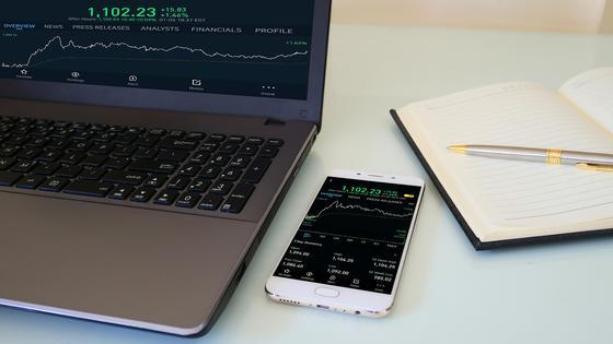 Телефон с программой для инвестирования лежит на столе рядом с блокнотом