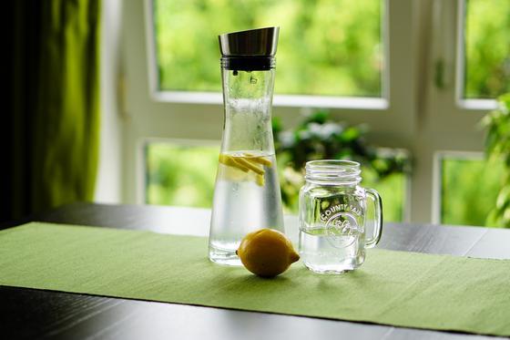Кувшин с водой, чашка с водой и лимон на столе