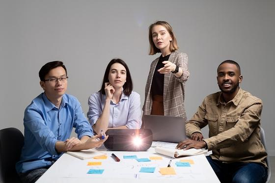 Четверо сотрудников за столом с проектором
