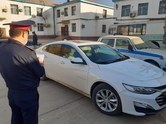 Полицейский стоит рядом с изъятой машиной в Туркестанской области