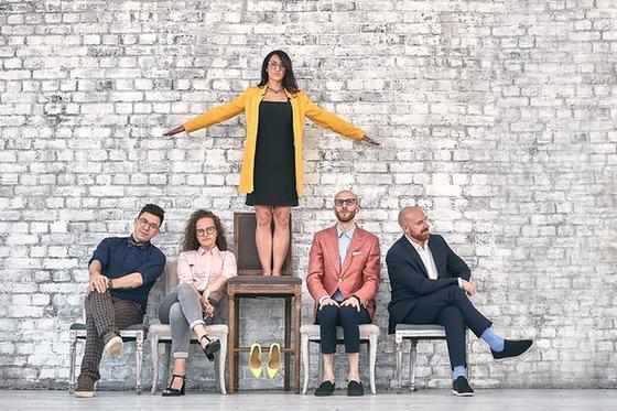 Женщина стоит на стуле, четверо сотрудников сидят на стульях