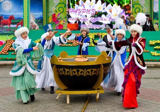 Девушки в национальных костюмах танцуют вокруг казана