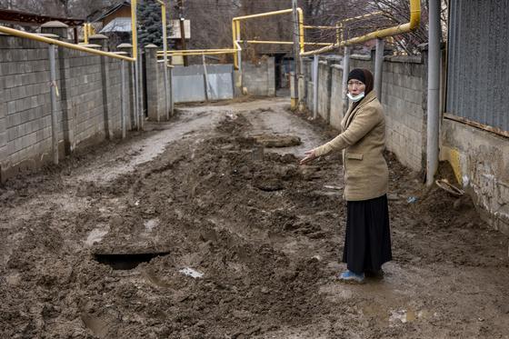 Женщина стоит посреди улицы в грязи