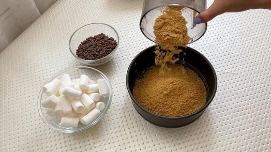 Измельченное печенье в форме для выпекания, зефир и шоколад