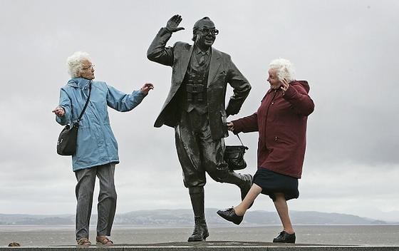 Две бабушки танцуют возле памятника