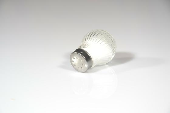 Соль в солонке на белом фоне