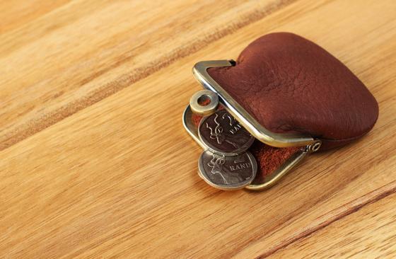 Кожаный кошелек с монетами лежит на столе