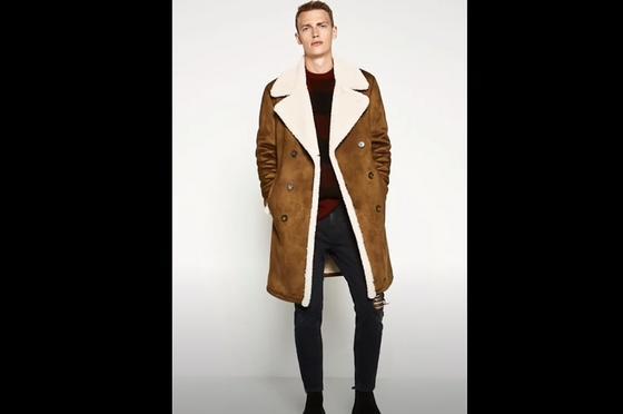 Мужчина в меховом пальто стоит у стены