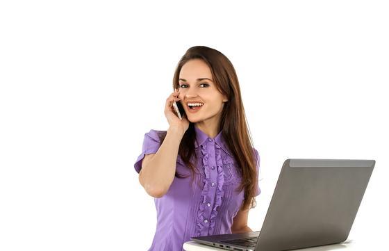 Женщина с ноутбуком говорит по телефону