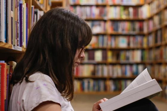 девочка читает книгу в библиотеке