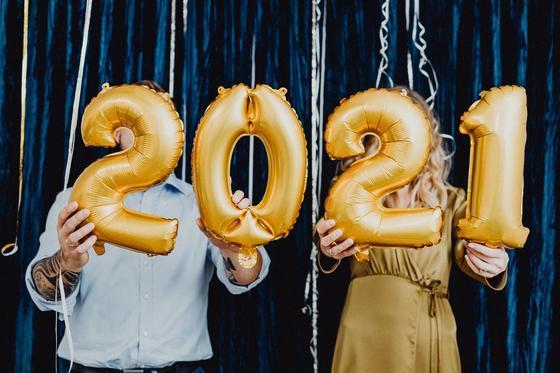 парень и девушка держат шарики в виде цифр 2021