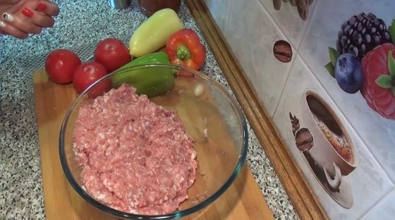Мясной фарш в стеклянной миске, овощи на доске