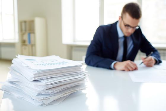 Офисный работник с кипой бумаг на столе