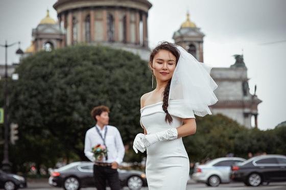 Невеста в белом платье на фоне жениха, машин и городского пейзажа