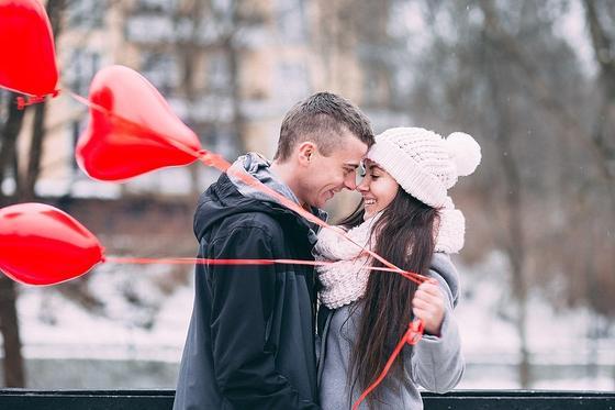 Парень обнимает девушку со связкой сердец-шаров
