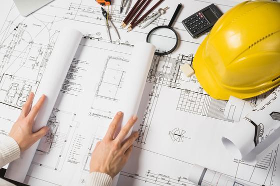 Мужчина держит план строительства
