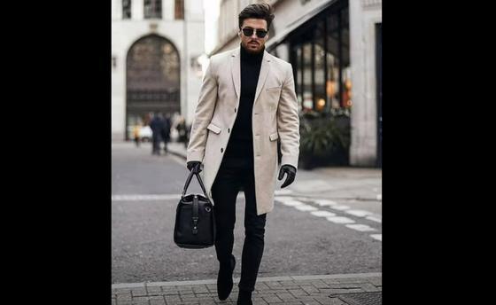 Мужчина в светлом пальто идет по улице