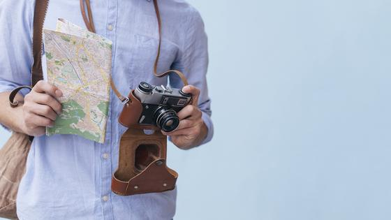 Турист с картой и фотоаппаратом
