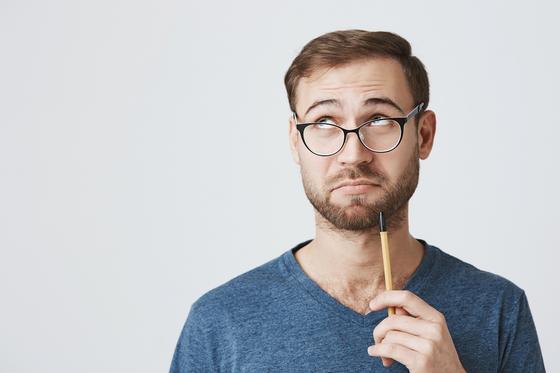 Мужчина в очках держит карандаш
