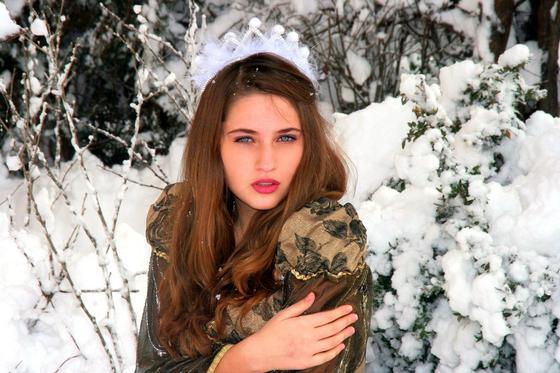 Девушка на фоне заснеженных кустов