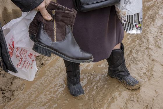 Женщина держит обувь в руках