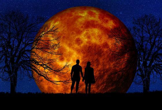 Пара держится за руки на фоне полной Луны