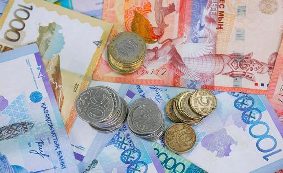 Монеты тенге лежат на купюрах тенге