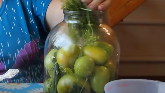 В банке наложены зеленые помидоры и зелень