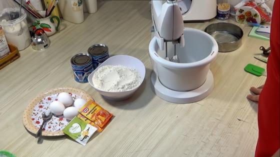 Яйца, сгущенка, мука и другие ингредиенты для торта возле миксера