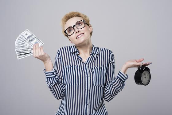 Женщина держит деньги и часы