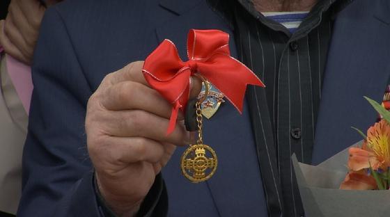 Мужчина держит в руке ключ с красным бантом