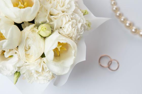 Обручальные кольца рядом с букетом и жемчугом